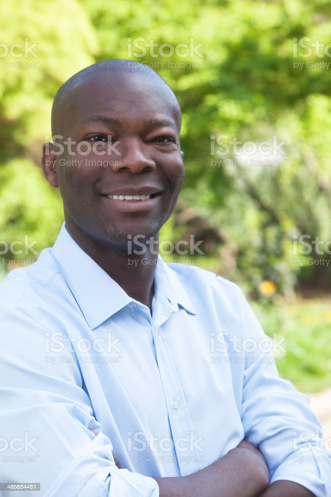 African man in park with crossed arms looking at camera stock photo