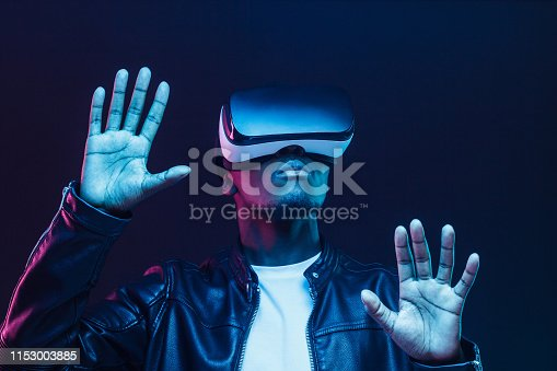 1090878574istockphoto African man in vr glasses, playing video games with virtual reality headset, trying to touch something with hands 1153003885