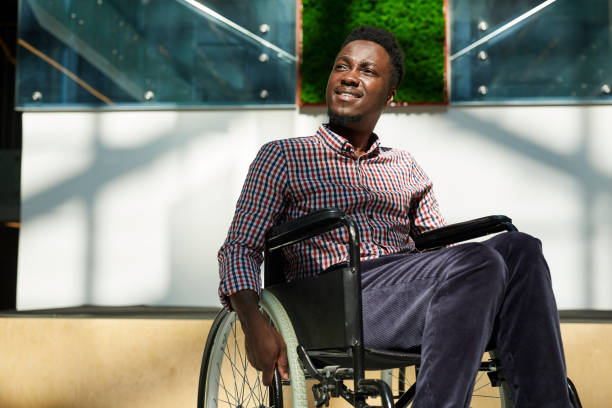 African man in wheelchair African man in wheelchair looking away and smiling at modern office paraplegic stock pictures, royalty-free photos & images