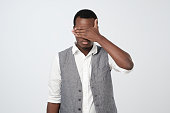 istock African man in white shirt and vest covering his face with hands 1069245170