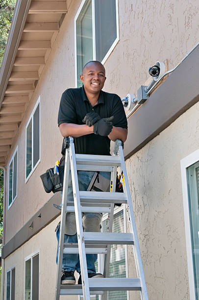 African man installing security camera stock photo