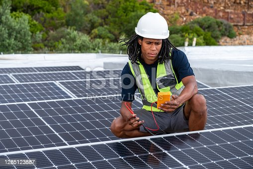 An African man with protective gear checks the voltage of the solar panels that he has just installed on a roof. African man installing renewable energy solutions