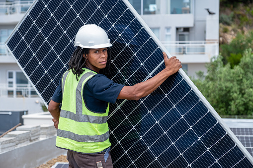 An African man with protective gear installs solar panels on a roof. African technician installs solar panels.