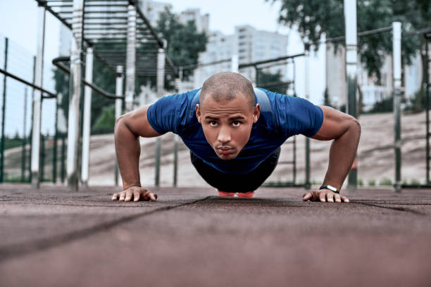 african man is doing plank at open air gym near the park - man city exercise abs foto e immagini stock