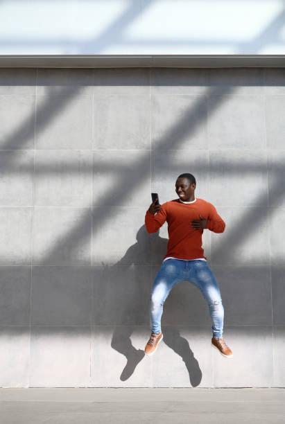 Afrikanischer Mann springen für Freude halten Telefon – Foto