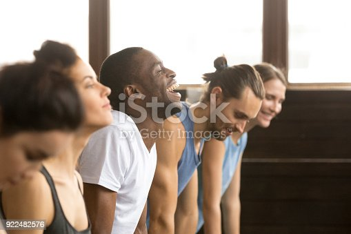 914755448istockphoto African man laughing doing yoga or plank at group training 922482576