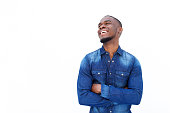 istock African man laughing with arms crossed against white background 513499828