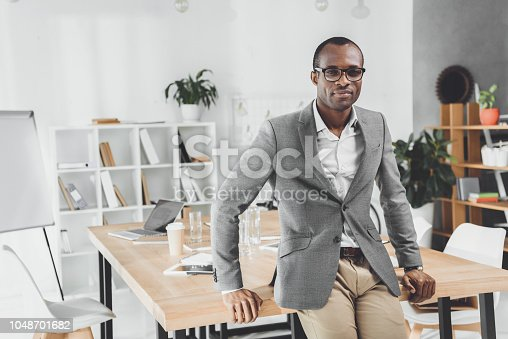 istock african man leaning on table and looking at camera at office space 1048701682