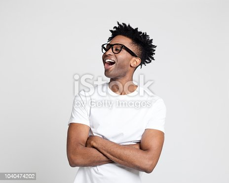 Portrait of afro american man with surprised expression, looking away at copy space and laughing on white background. Man in white t-shirt wearing nerd glasses with arms crossed.