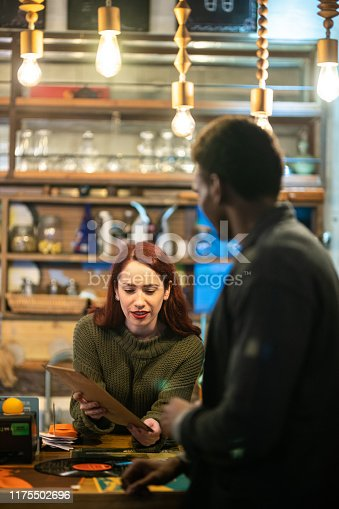Cheerful hipster multi-ethnic couple looking at vinyl LP record and talking in record store
