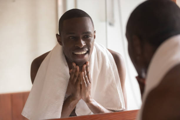 african man looking in mirror cleaning face after shaving - a petto nudo foto e immagini stock