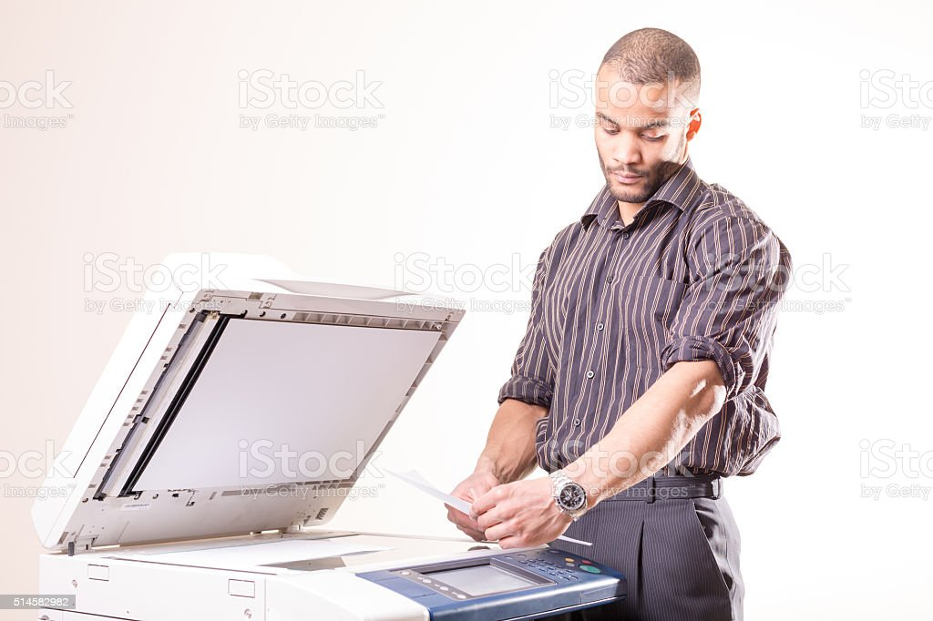 african man making copies of documents stock photo