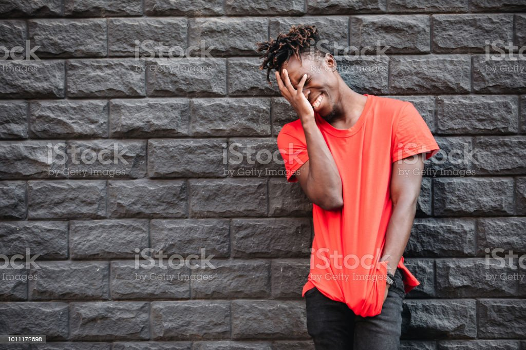 African man model laughing in red t-shirt against brick wall with...
