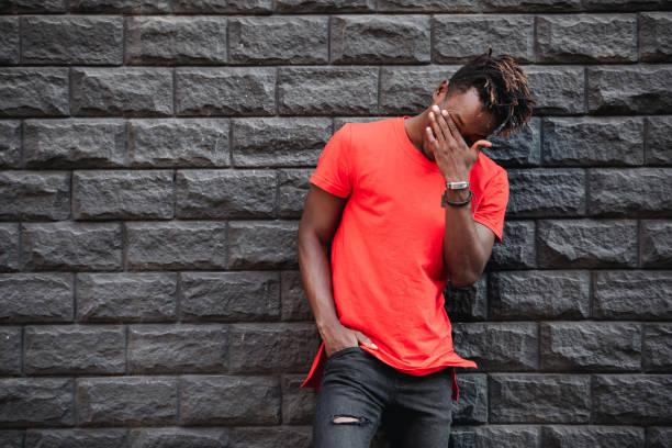 afrikanischer mann modell lachen im roten t-shirt gegen ziegelwand mit facepalm - rote dreads stock-fotos und bilder