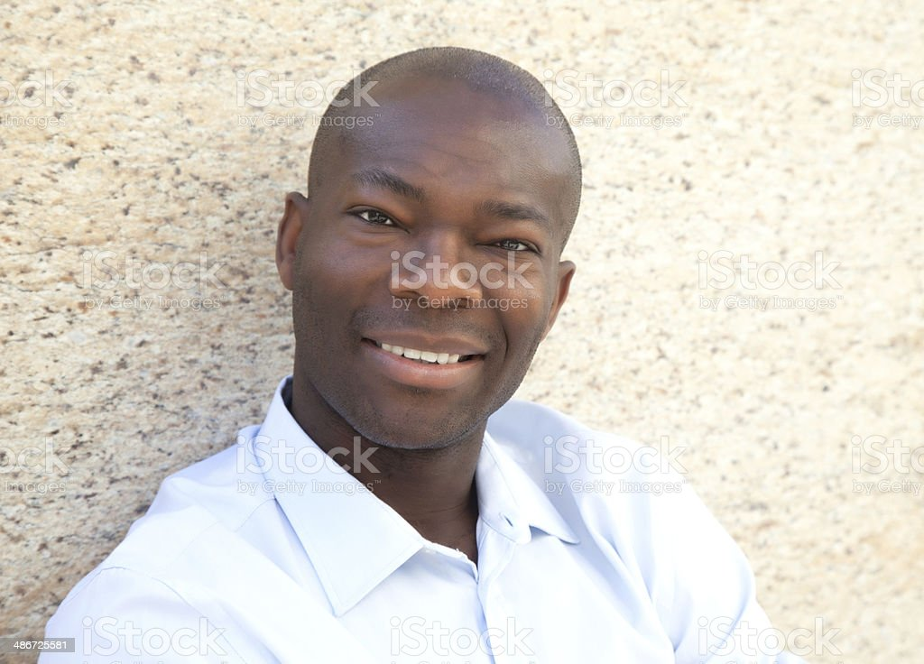 African man on a wall looking at camera stock photo
