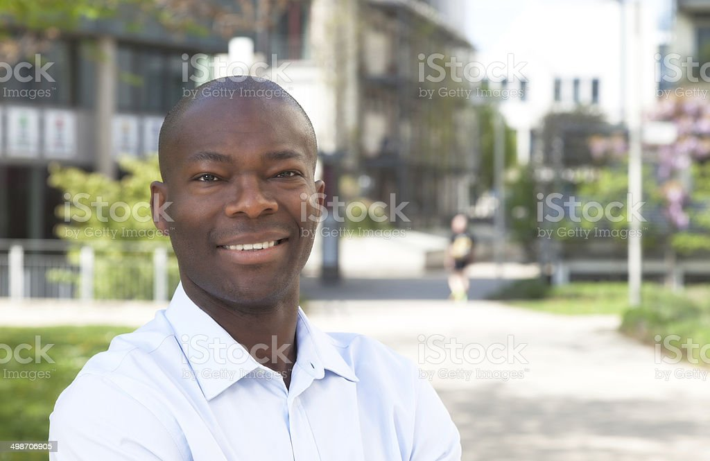African man outside laughing at camera stock photo