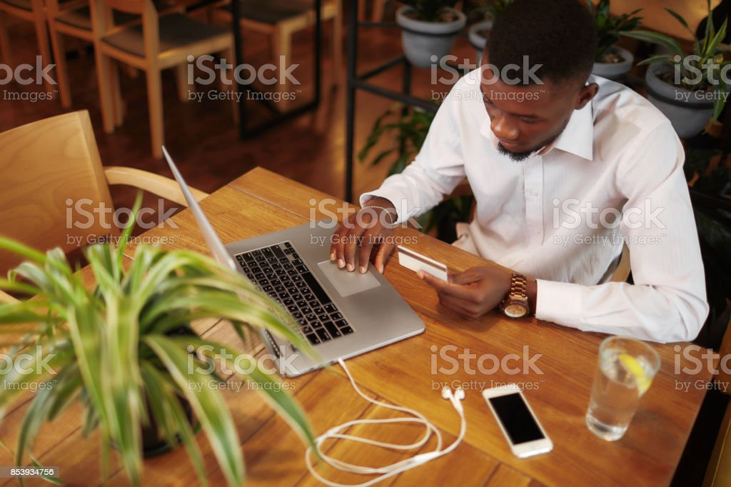 African man pay with and buying in internet shop stock photo