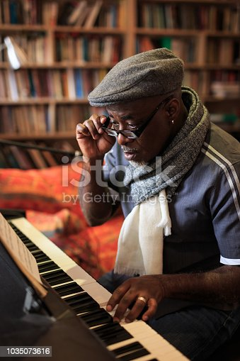 African man playing the piano at home