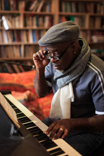 afrikanischer mann das klavierspiel zu hause - one song training stock-fotos und bilder