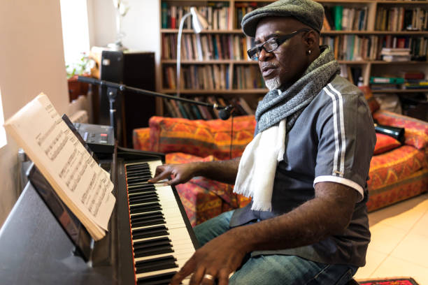African man playing the piano at home African man playing the piano at home, alone. keyboard player stock pictures, royalty-free photos & images
