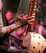 young african man plays a stringed instrument at live concert