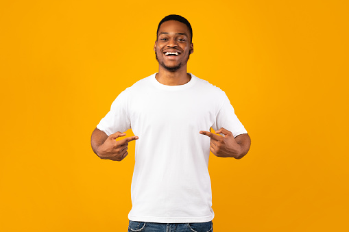 African Man Pointing At Himself Standing In Studio, Yellow Background