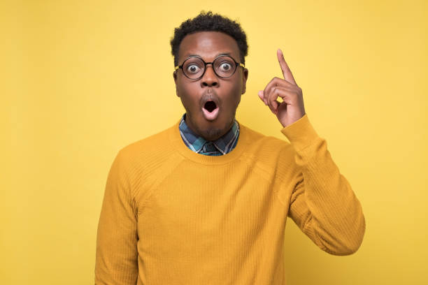 african man pointing upwards showing idea or eureka gesture. stock photo