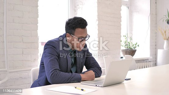 888751614 istock photo African Man Reading Email on Laptop 1126411429