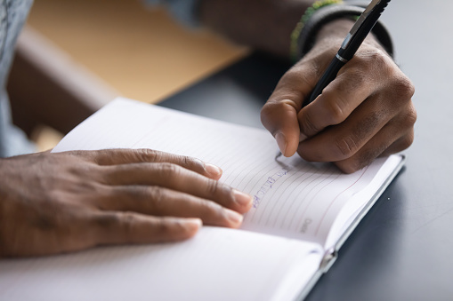 African man sit at desk hold pen keeps startup business ideas, plans, creative thoughts to notebook close up image. Makes appointment notes time, writes important things and to-do list not to forget