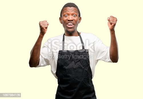925466128 istock photo African man shop owner wearing apron happy and excited celebrating victory expressing big success, power, energy and positive emotions. Celebrates new job joyful 1097584126
