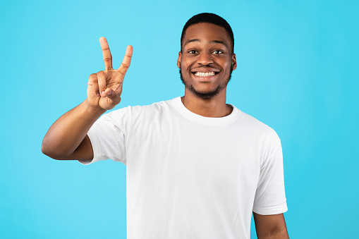 African Man Showing Number Two Posing On Blue Studio Background