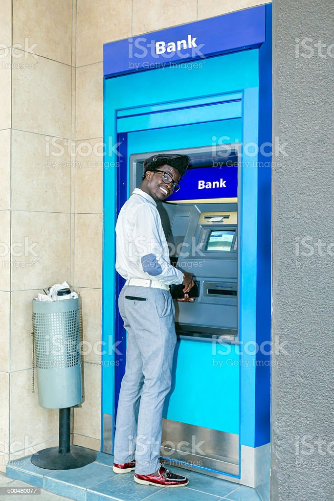 African man smiling at the ATM bank teller stock photo