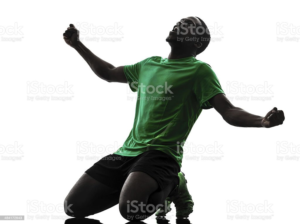 african man soccer player celebrating victory silhouette stock photo