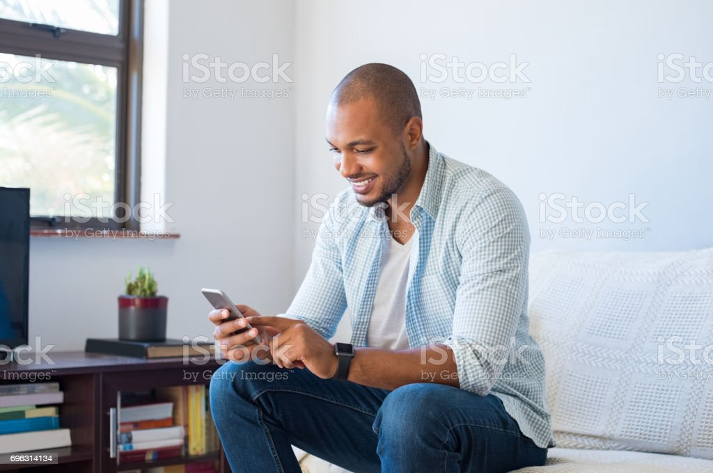African man typing phone message stock photo