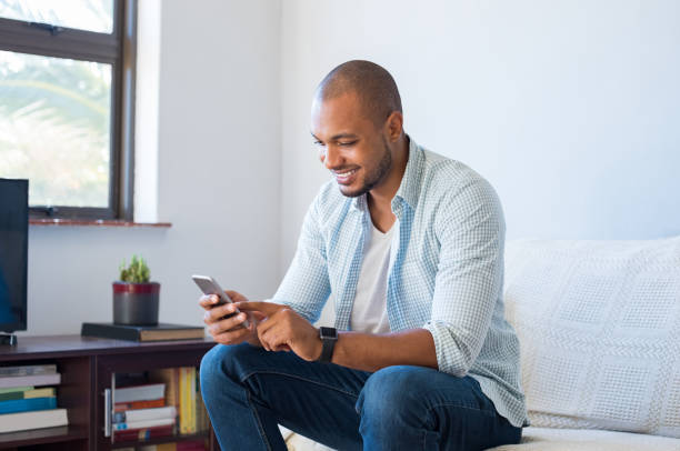 african man typing phone message - mobile game stock photos and pictures