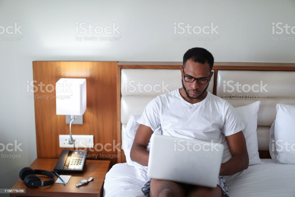 African man using a laptop in his hotel room.