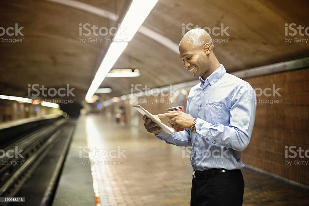 African man using digital tablet while waiting for subway royalty-free stock photo