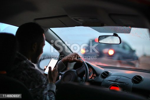African man using his phone while driving in the rain.