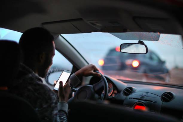 비에서 운전 하는 동안 자신의 휴대 전화를 사용 하는 아프리카 사람. - 부주의한 뉴스 사진 이미지