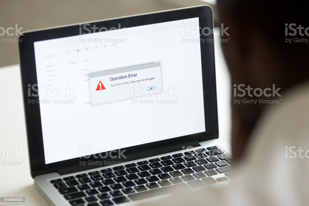 African man using laptop with application failure message on screen stock photo