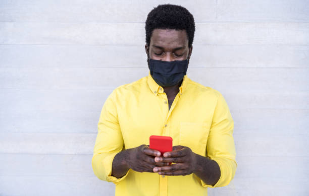 african man using mobile phone while wearing face protective mask outdoor - black person watching videos on smartphone during coronavirus outbreak - covid 19 lifestyle - focus on face - afro latino mask imagens e fotografias de stock