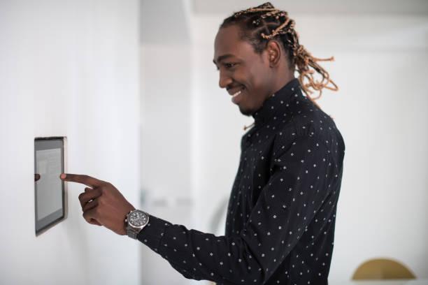 Afrikanischer Mann mit Smart-Home-Bildschirm – Foto