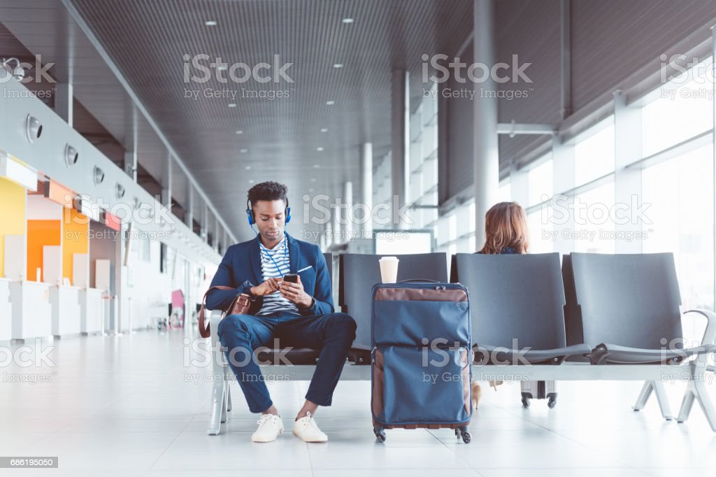 African man waiting for his flight at the airport lounge stock photo