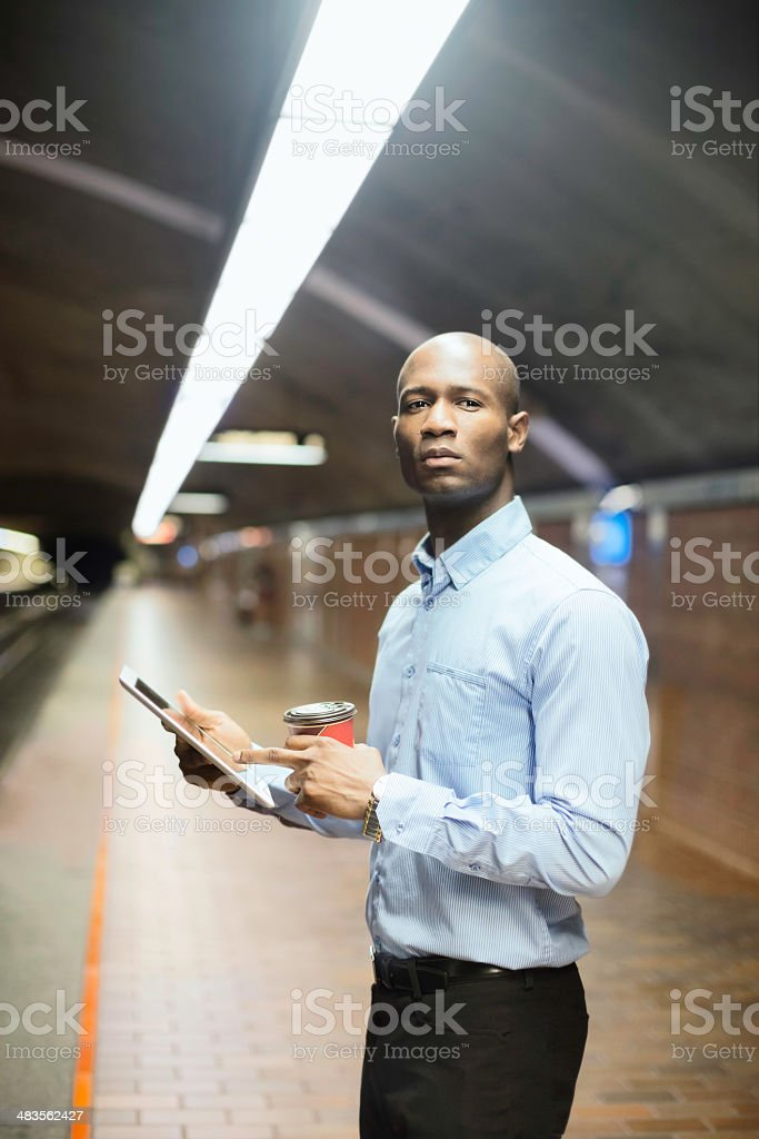 African man waiting for subway with tablet and coffee vertical royalty-free stock photo