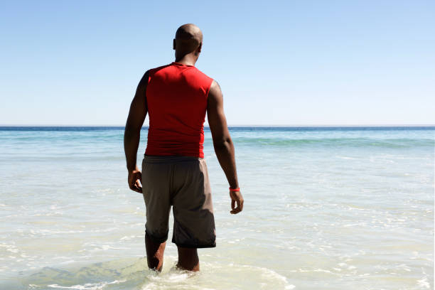 African man walking in to the sea water Rear view portrait of african man walking in to the sea water wading stock pictures, royalty-free photos & images