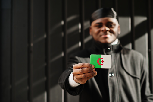 African man wear black durag hold Algeria flag at hand isolated dark background.