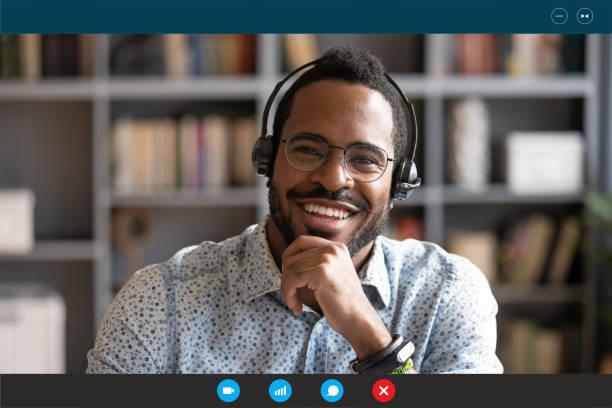 Afrikanischer Mann tragen Headset sitzen am Schreibtisch und schauen auf die Kamera – Foto