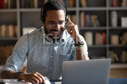 Focused African man sitting at desk wear headset watching webinar video course gain new knowledge use on-line application website. Manager talk to client provide professional help and support concept