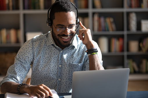 African man wear headset watching webinar video course