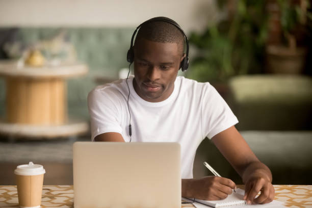 african man wearing headphones watching webinar making notes study online - didattica a distanza foto e immagini stock